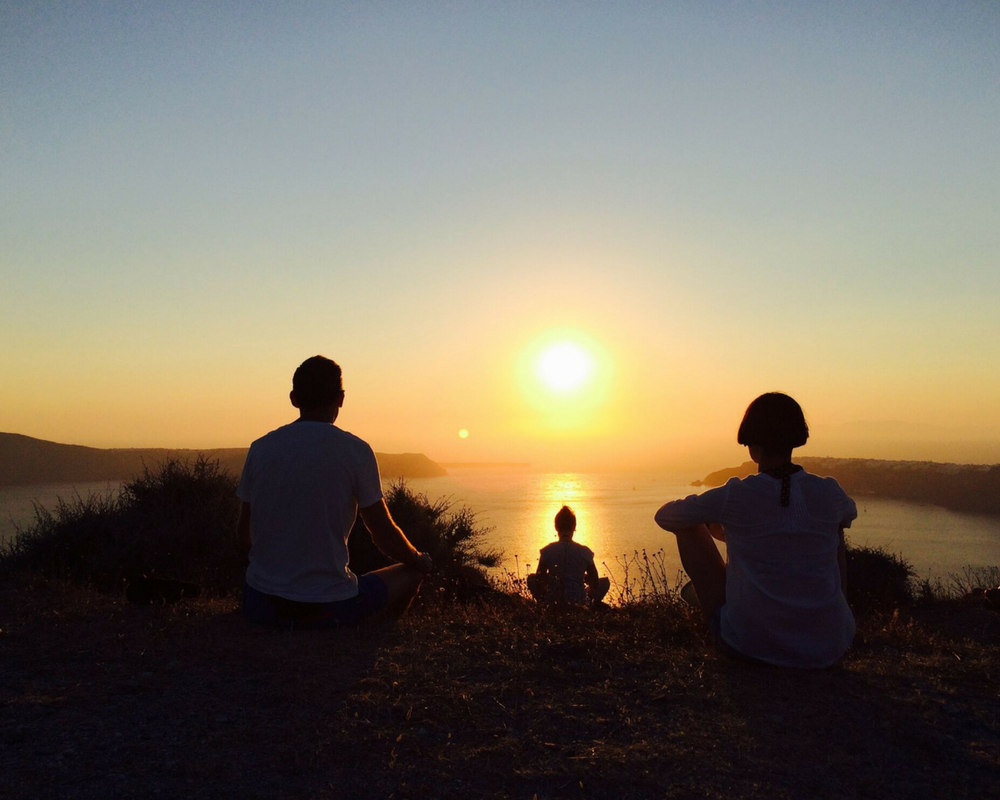 Yogis watching sunset over the sea