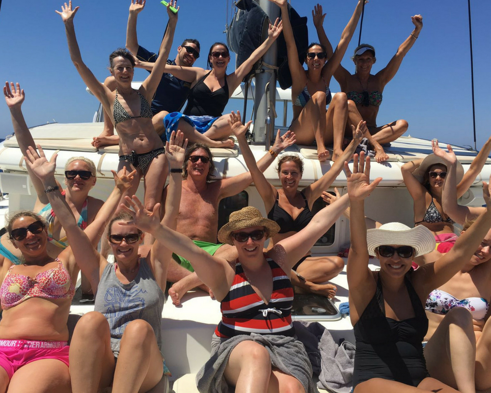 Yogis with arms in air on the boat