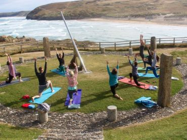 kneeling lunge people in circle doing yoga on cliffs next to sea easter cornwall yoga retreat