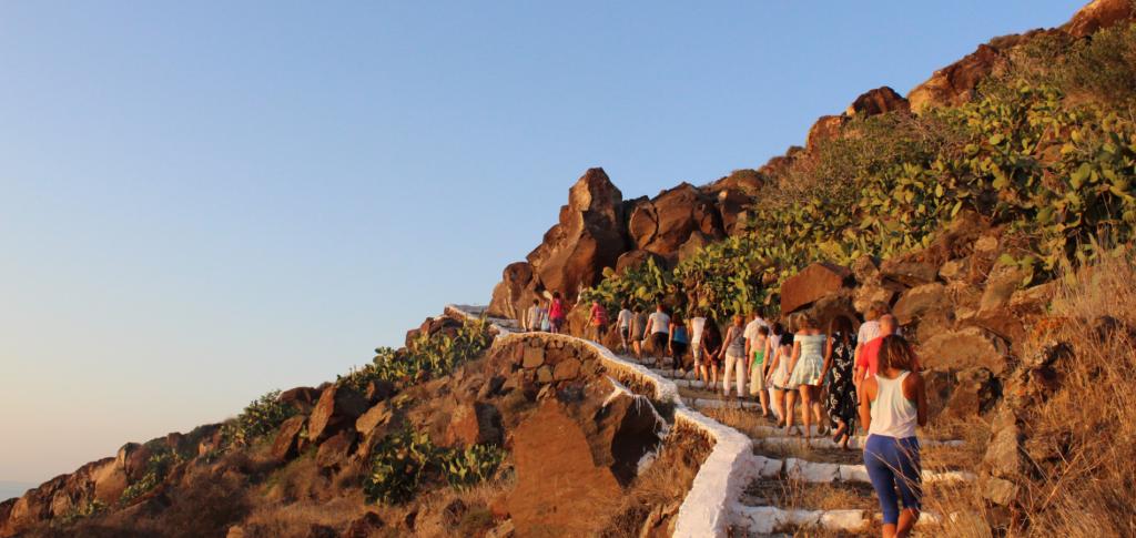 guests walking up hillside santorini sunset