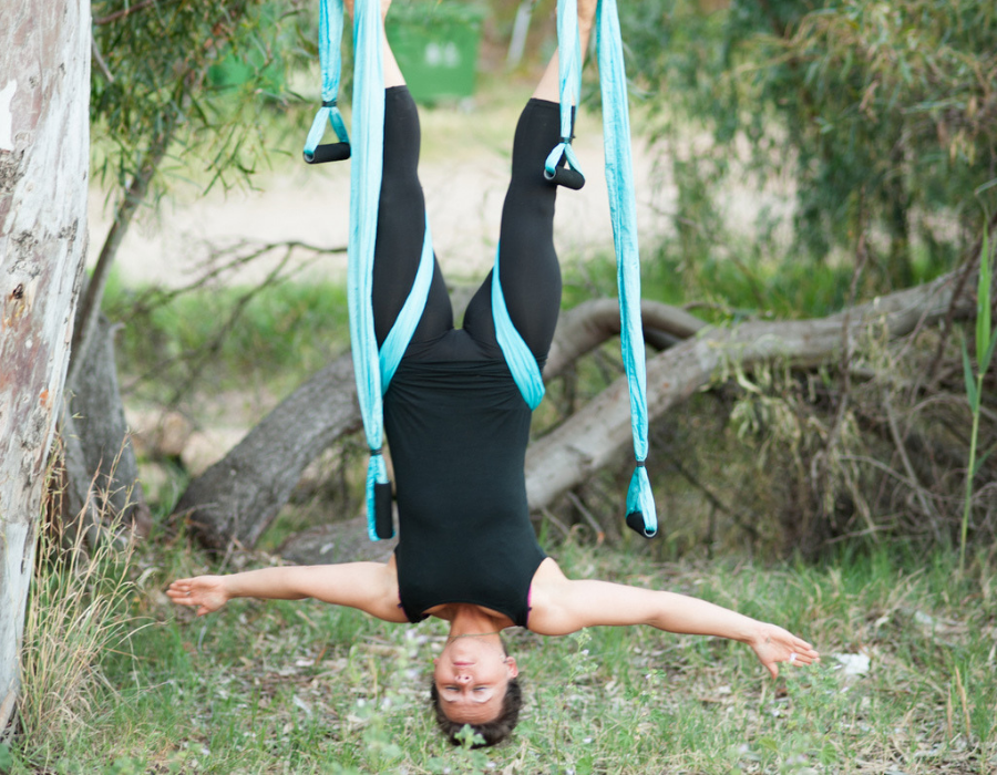 girl hanging upside down using yoga swing in tree