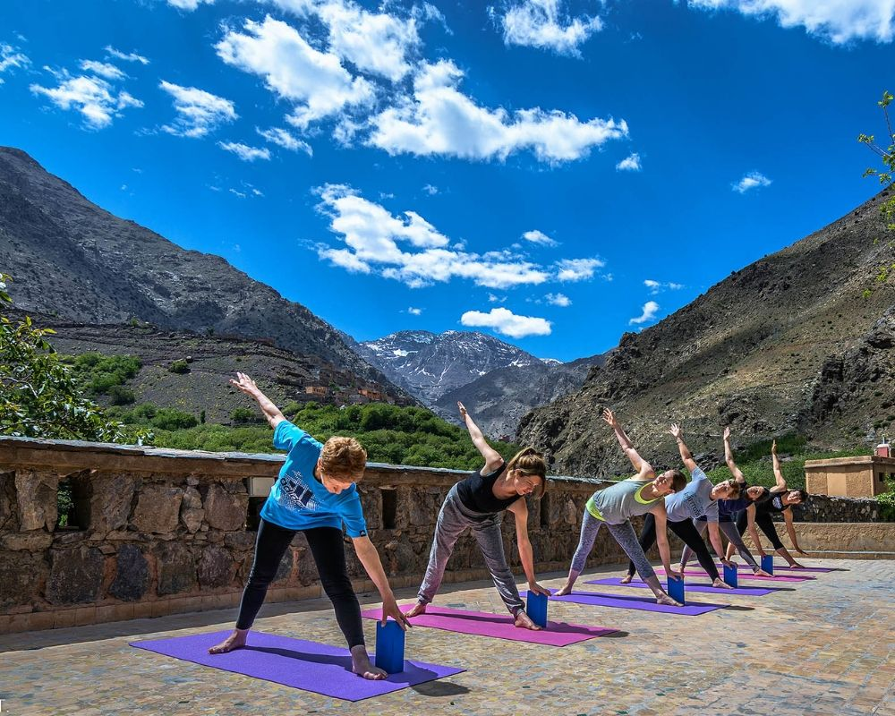 six people in triangle pose outside atlas mountains