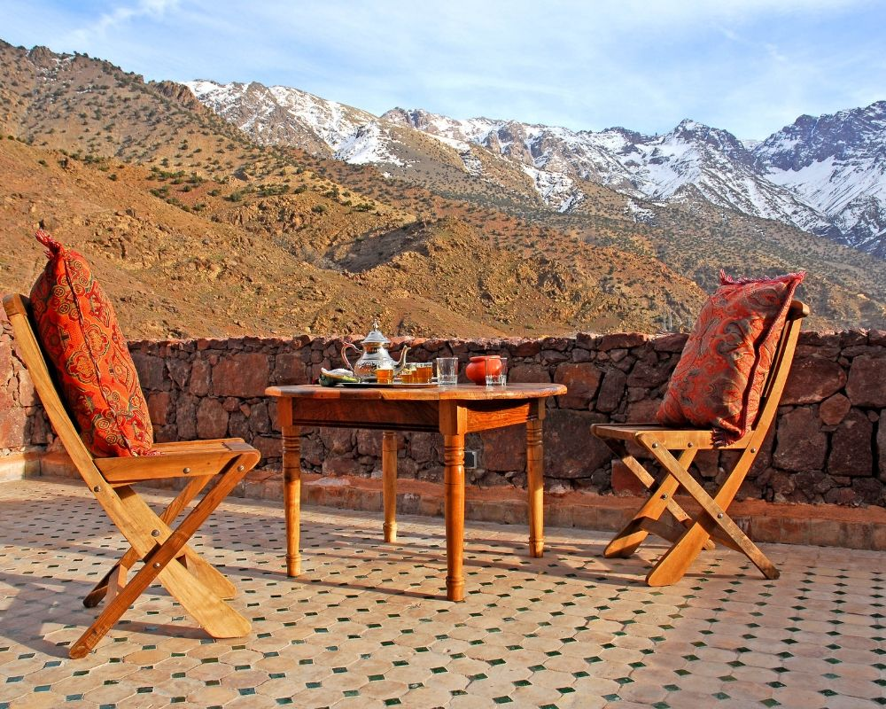 two charis and table in atlas snowcapped mountains