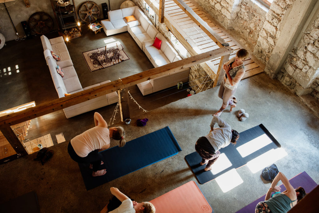 aerial image yoga teacher walking and people doing side twist in prayer on mats - hiking yoga holiday montenegro