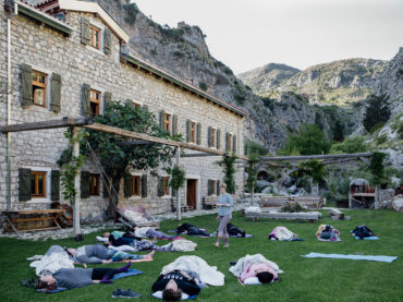 people in savasana outside front of olive mill accommodation - hiking yoga holiday montenegro