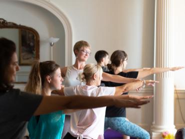 yoga class warrior 2 pose and yoga teacher easter wellness yoga retreat bicester
