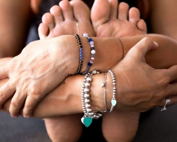 person in forward fold arms around feet head down bracelets on wrists